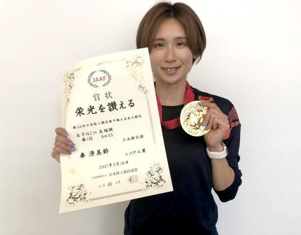 賞状とメダルを持つ秦選手