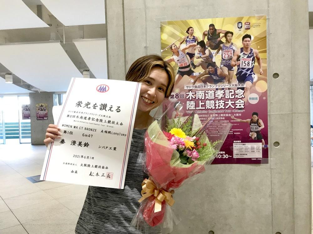 賞状と花束を持つ秦選手
